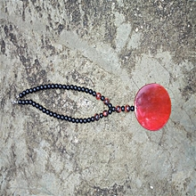 black beaded necklace with red pendant