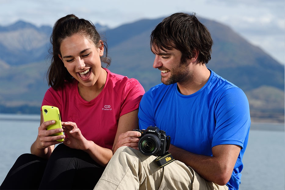 Photo of a man and woman looking at images on a smartphone, that were shot with the D7500