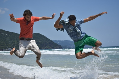 D3400 photo of two guys jumping over waves in the ocean