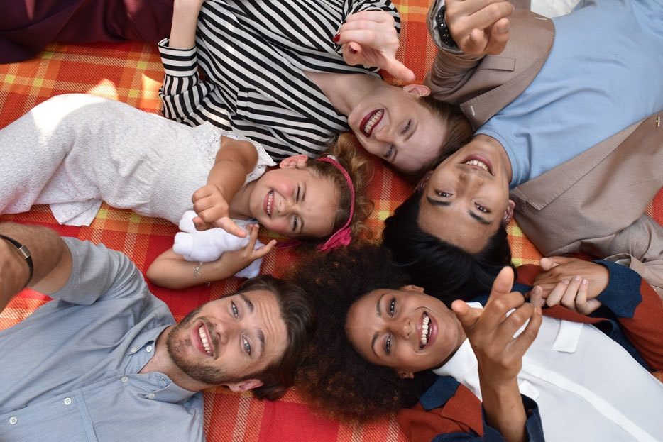 Nikon D5600 DSLR photo of a group of people lying on the floor looking up at the camera