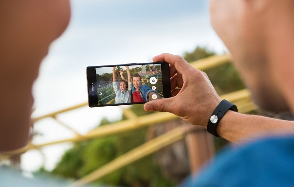 Couple using the Xperia Z3+ to take a selfie on a roller coaster